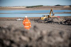 Worker and digger near lake at  surface coal mine restoration Stock Photos