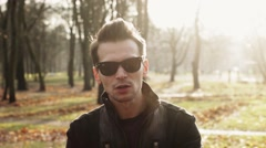 Portrait man in sunglasses hold both hands together in camera and walk away Stock Footage