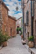 Narrow cobbled street with flowers in the old village Tourrettes-sur-Loup , F - stock photo