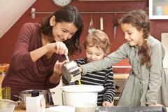 Mother and children cooking in kitchen Stock Photos