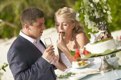 Lovely couple eating wedding cake during tropical marriage ceremony. Stock Photos