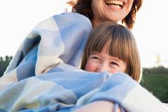 Mother and daughter wrapped in blanket Stock Photos