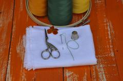 variety of objects for needlework orange on the wooden table - stock photo