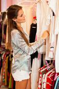 Woman shopping for clothes in store Stock Photos