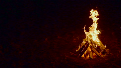 Outdoor wood campfire burring brightly at night forest with sparks - stock footage