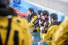 Offshore oil workers being trained in survival techniques in pool facility Stock Photos