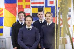 Portrait of nautical students standing in front of signalling flags - stock photo