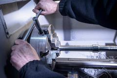 Engineer using tool to tighten industrial steel lathe - stock photo