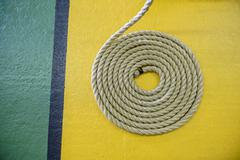 Overhead view of coiled rope on yellow and green floor in nautical training Stock Photos