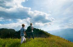 Father and son hiking on grassy hilltop - stock photo