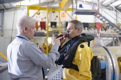 Tutor teaching offshore oil worker survival training in pool facility Stock Photos