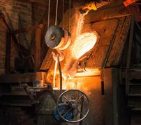 Worker adding flux to molten metal in foundry Stock Photos