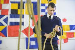 Nautical student standing in front of signalling flags and tying reef knot with - stock photo