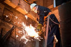 Worker cleaning surface of molten metal in foundry Stock Photos