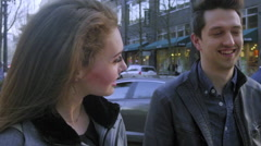 On a city street, a cute couple smile and laugh together - stock footage