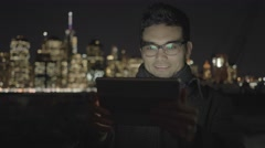 Portrait shot of handsome asian man browsing the web on tablet pc Stock Footage
