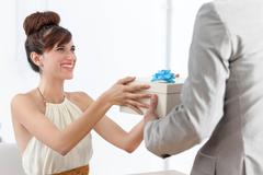 Man giving smiling girlfriend present Stock Photos