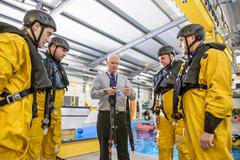 Tutor teaching offshore oil workers survival training in pool facility Stock Photos