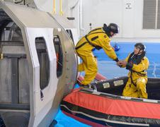 Offshore oil workers training in escape from helicopter simulator at training - stock photo