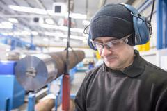 Close up of engineer wearing safety glasses and ear defenders next to crane and Stock Photos