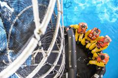 Offshore oil workers training in net escape simulation at training pool facility - stock photo
