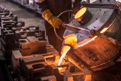 Worker pouring molten steel into moulds in foundry Stock Photos