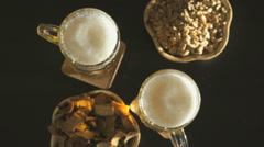 Two hands with mugs of beer. Nuts and crackers Stock Footage
