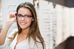 Woman trying on glasses in store Stock Photos