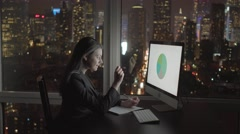 Attractive sales women working on pc in modern city office at night Stock Footage
