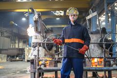 Portrait of worker in foundry wearing visor and holding flame gun - stock photo