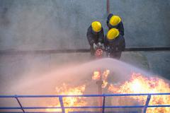 Three firefighters putting out fire in fire simulation training facility, Stock Photos