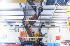 Offshore oil workers training in net escape simulation at training pool facility Stock Photos