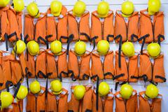 Survival equipment of orange lifejackets and yellow hardhats hanging on wall in Stock Photos