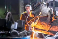 Worker pouring molten metal into moulds in foundry Stock Photos
