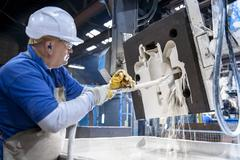Worker coating sand mould in foundry Stock Photos