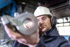 Worker using torch to inspect cast metal parts in foundry Stock Photos