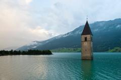 Clock tower submerged in rural lake - stock photo
