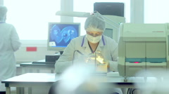 Scientist looks at object under magnifying glass with laboratory equipment Stock Footage