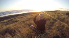 Man sitting in sand dunes takes photo of a beach sunset using smart phone Stock Footage