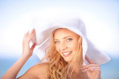 Woman wearing floppy hat outdoors - stock photo