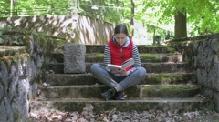 The girl in a red jacket and a striped sweater, reading a big book. Slow motion. Stock Footage