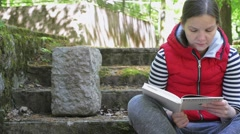 The girl in a red jacket and a striped sweater, reading a white book. Stock Footage