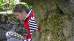 The girl in a red jacket and a striped sweater, reading a white book. Slow. Stock Footage
