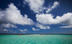 Clouds over sandbar and tropical water Stock Photos