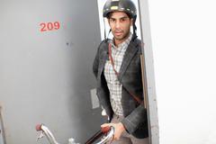 Man wheeling bicycle out apartment door Stock Photos