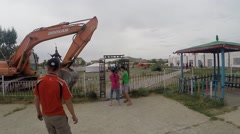 People Pass Through a Passage in an Iron Fence Near Which Stands Tractor View Stock Footage