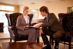 Business people talking in hotel lobby Stock Photos