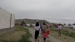 People go Along Way Near Stadium Next to Mongolian Yurts Stock Footage