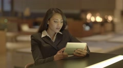Beautiful black woman using smart phone tablet computer sitting inside at night Stock Footage