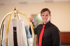 Porter with luggage cart in hotel lobby Stock Photos